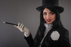 Kvinnlig trollkarl i dräktdräkt med den magiska pinnen som gör trick Royaltyfria Foton