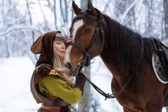 Kvinnlig trollkarl med en häst i vintern royaltyfri bild