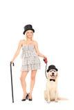 Kvinnlig trollkarl som rymmer en hund på en koppel Arkivbild