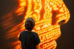 Kvinnlig turist, i svart bekläda anseende och att se samtida konst av den mänskliga framsidan Fantastisk färgbelysning på mänskli arkivbild