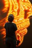 Kvinnlig turist, i svart bekl?da anseende och att se samtida konst av den m?nskliga framsidan Fantastisk f?rgbelysning p? m?nskli royaltyfri bild
