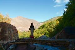 Kvinnlig turist- korsning en skuggig bro i kartbokbergen royaltyfri fotografi