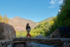 Kvinnlig turist- korsning en spång i kartbokbergen royaltyfri bild