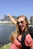 Kvinnlig turist- resande på Rio de Janeiro som pekar på KristusFörlossare. arkivbild
