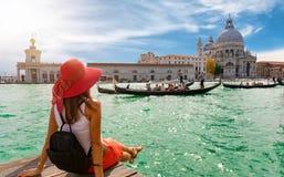 Kvinnlig turist som ser basilikadina Santa Maria della Salute och Canale som är stora i Venedig, Italien arkivfoto