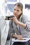 Kvinnlig underhållstekniker som kontrollerar bilmålarfärg med utrustning i seminarium arkivbild