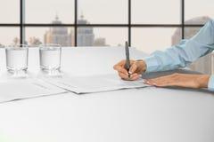 Kvinnlig undertecknande legitimationshandlingar för kontorsanställd arkivbilder