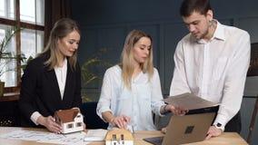 Kvinnlig ung arkitekt som arbetar på byggande plan, medan komma hennes coworker två och att starta diskutera idéer av designen arkivfilmer