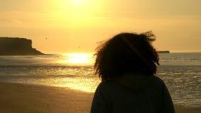 Kvinnlig ung kvinna med anseende för lockigt hår på en strand som ser solnedgång eller soluppgång stock video