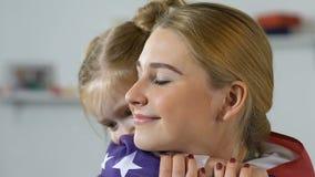 Kvinnlig unge som täcker den militära kvinnanationsflaggan som kysser kinden, amerikansk nation lager videofilmer