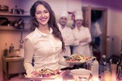 Kvinnlig uppassare som tar maträtten på kök royaltyfria bilder