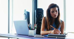 Kvinnlig utövande användande bärbar dator på skrivbordet 4k arkivfilmer