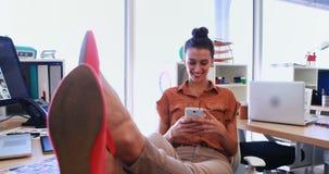 Kvinnlig utövande användande mobiltelefon på hennes skrivbord 4k lager videofilmer