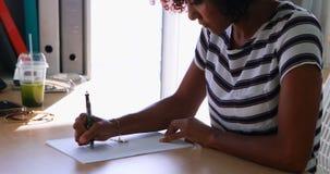 Kvinnlig utövande handstil på papper på hennes skrivbord 4k lager videofilmer