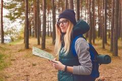 Kvinnlig utforskare med översikten som är utomhus- i skogen i höst arkivfoton