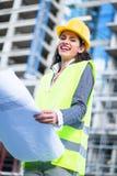 Kvinnlig väg-och vattenbyggnadsingenjör som studerar utkast som besöker konstruktionsplatsen royaltyfri bild