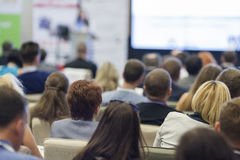 Kvinnlig värd som framme talar av de stora åhörarna under affärskonferens arkivfoto