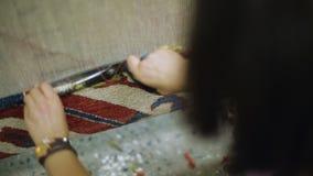 Kvinnlig väva matta som klipper vävde trådar med sax, traditionellt hantverk arkivfilmer