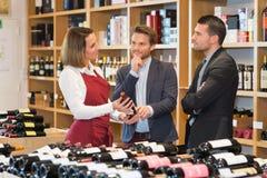 Kvinnlig vinförsäljare som hjälper klienter royaltyfri bild