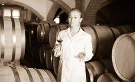 Kvinnlig vinhusarbetare som kontrollerar kvalitet av produkten Arkivbild