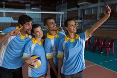 Kvinnlig volleybollspelare med laget som tar selfie Royaltyfria Bilder