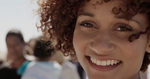 Kvinnlig volontär som ser kameran på stranden 4k lager videofilmer