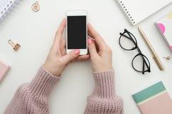 Kvinnlig workspacemodell med smartphonen i kvinnliga hand-, anteckningsbok-, anblick-, notepad-, penn- och kontorstillförsel plan arkivfoto