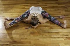 Kvinnlig yogamodell över huvudet Kurmasana Tortoise Pose Arkivfoton