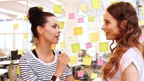 Kvinnliga affärsledare som påverkar varandra medan läs- klibbiga anmärkningar lager videofilmer