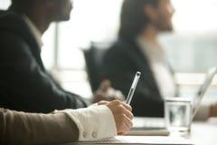 Kvinnliga anmärkningar för danande för hållande penna för hand på mötet, closeupsikt royaltyfri fotografi