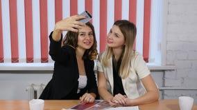 Kvinnliga arbetare för nätt ungt kontor som gör selfie Kontorslivbegrepp Tycka om fri tid på arbete Skjutit i 4k stock video