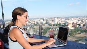 Kvinnliga arbeten på en dator i ett takkafé med en panoramautsikt av Pattaya arkivfilmer