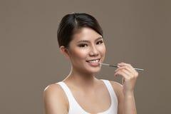 Kvinnliga asiatiska applicerande lipgloss Arkivbilder