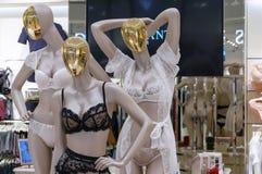 Kvinnliga attrapper med guld- framsidor i spets- underkläder arkivbilder