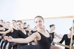 Kvinnliga balettdansörer som öva på barren Arkivfoto