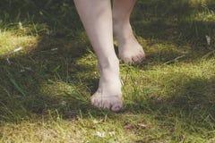 Kvinnliga barfota ben som går i skogen Arkivbild