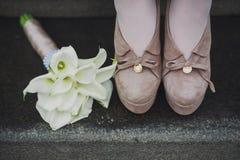 Kvinnliga ben i modebruntskor och den vita härliga buketten av vita blommor Royaltyfri Foto