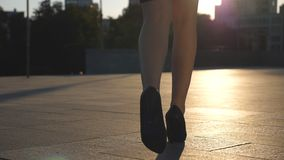 Kvinnliga ben i skor för höga häl som går i den stads- gatan med solsignalljuset på bakgrund Fot av den unga affärskvinnan lager videofilmer