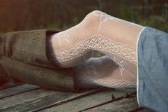 Kvinnliga ben i vit snör åt strumpor och kängor Royaltyfri Foto
