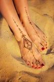 Kvinnliga ben med hennatatueringen på stranden sandpapprar bakgrund Fotografering för Bildbyråer