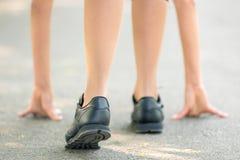 Kvinnliga ben och h?nder som ?r p?lagda asfaltn?rbilden, symbol av starten f?r k?rningen, stark personlighet och maratonk?rning royaltyfria bilder