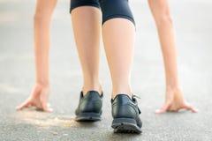 Kvinnliga ben och h?nder som ?r p?lagda asfaltn?rbilden, symbol av starten f?r k?rningen, stark personlighet och maratonk?rning royaltyfri foto