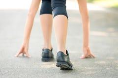 Kvinnliga ben och h?nder som ?r p?lagda asfaltn?rbilden, symbol av starten f?r k?rningen, stark personlighet och maratonk?rning arkivbilder