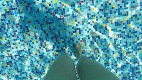 Kvinnliga ben som promenerar botten av pölen Punkt av sikten av kvinnan som kliver på simbassängen under sommarsemester POV arkivfilmer