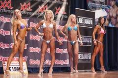 Kvinnliga bikinikonditionkonkurrenter som visar deras bästa i en lineup arkivbild