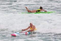 Kvinnliga bränninglifesavers som utbildar med surfingbrädor royaltyfri foto