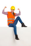 Kvinnliga byggnadsarbetareSitting And Flexing muskler arkivbild