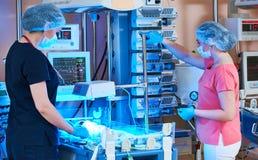 Kvinnliga doktorer av intensivvårdenheten för nyfött spädbarn behandla som ett barn framme Royaltyfri Bild