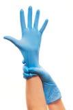 Kvinnliga doktorns händer som sätter på blått, steriliserade kirurgiska handskar royaltyfria foton