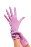Kvinnliga doktorns händer som sätter på lilor, steriliserade kirurgiska handskar Royaltyfria Bilder